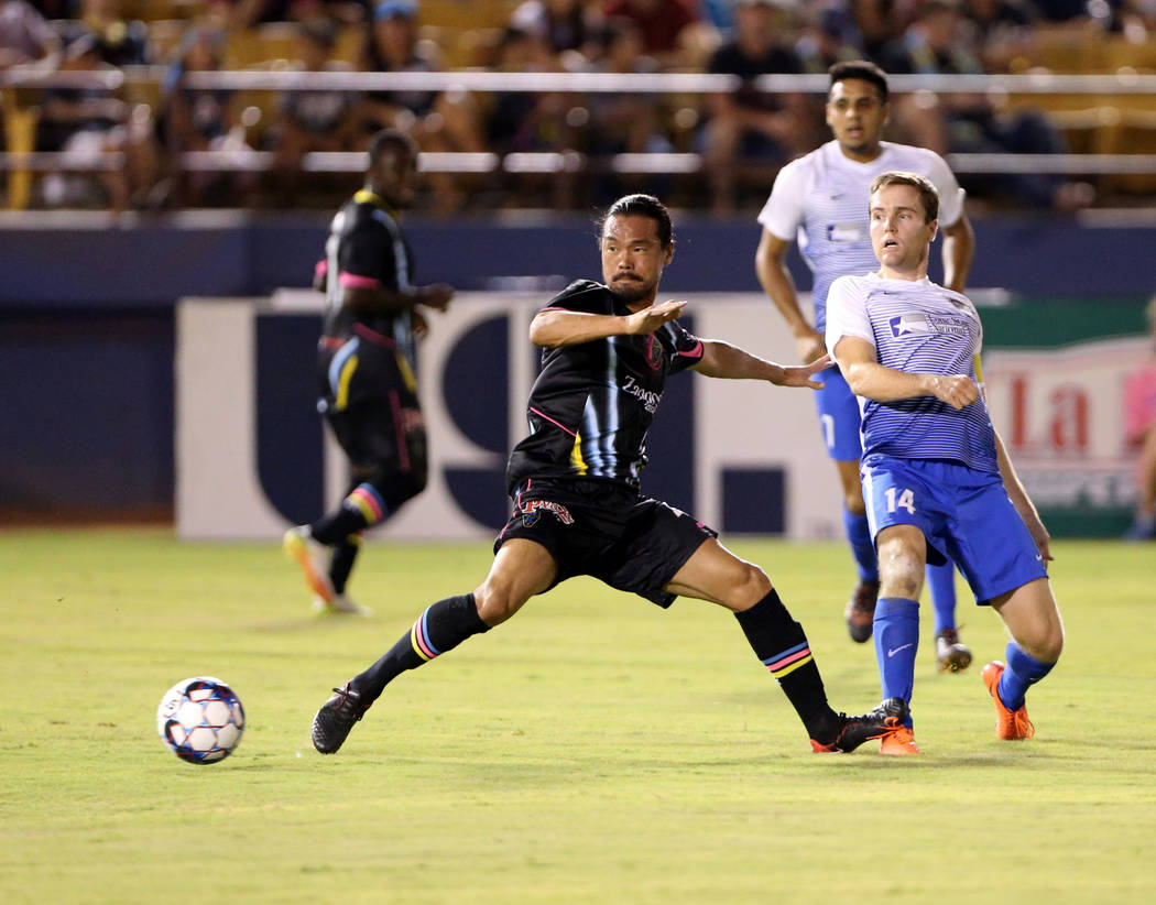 El centrocampista del Las Vegas Lights FC, Daigo Kobayashi, va por el balón frente al centrocampista del Toros Valley FC, Todd Wharton (14), en la primera mitad de un partido de fútbol en Cashma ...