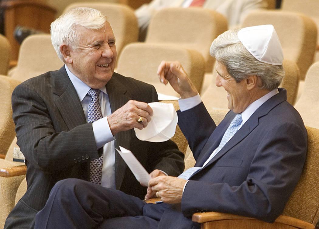 El ex senador Paul Laxalt, republicano por Nevada, izquierda, le pide al senador John Kerry, demócrata por Massachusetts, ayuda con su yarmulke antes del comienzo del funeral del ex senador Chic ...