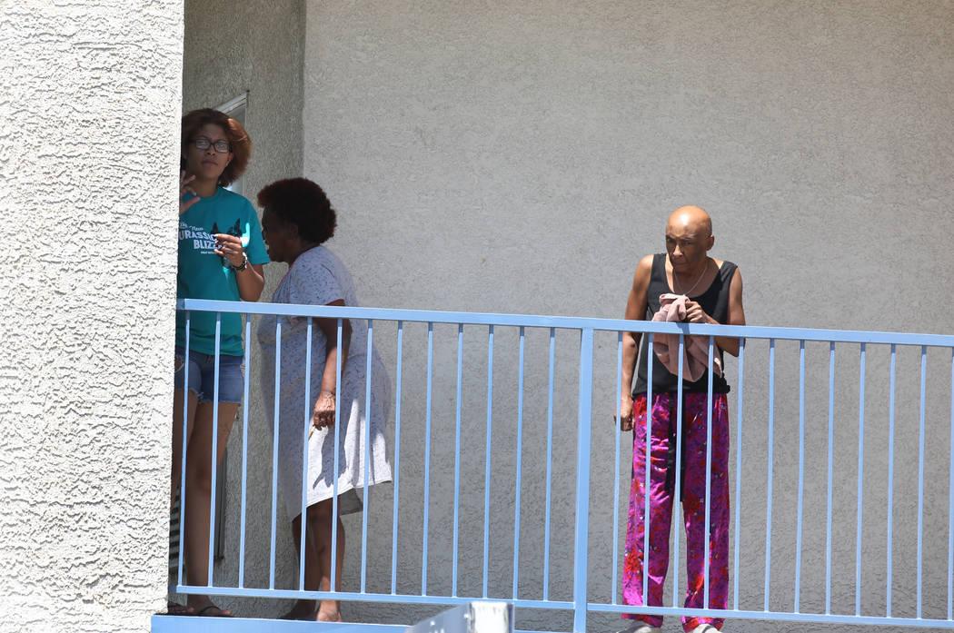 Los residentes de Kensington Suites en la cuadra 2200 de West Bonanza Road miran mientras la policía de Las Vegas está investigando un tiroteo que involucró a un oficial, el lunes 6 de agosto d ...