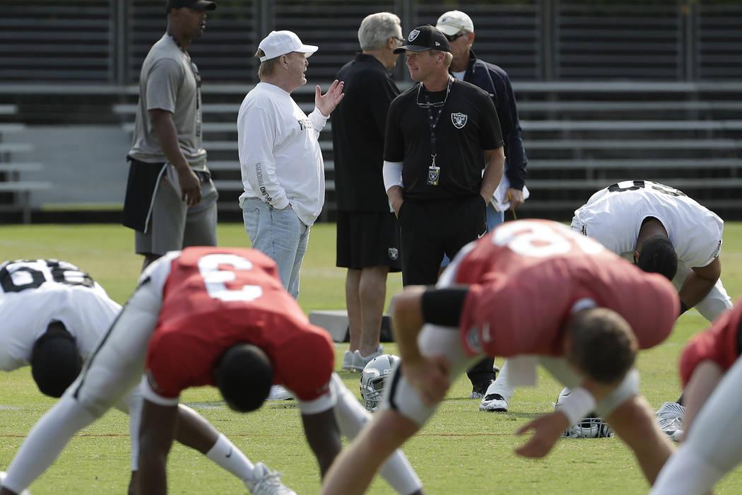 El propietario de los Oakland Raiders, Mark Davis, centro izquierda, habla con el entrenador en jefe Jon Gruden mientras los jugadores se estiran durante la práctica de fútbol de la NFL en Napa, ...