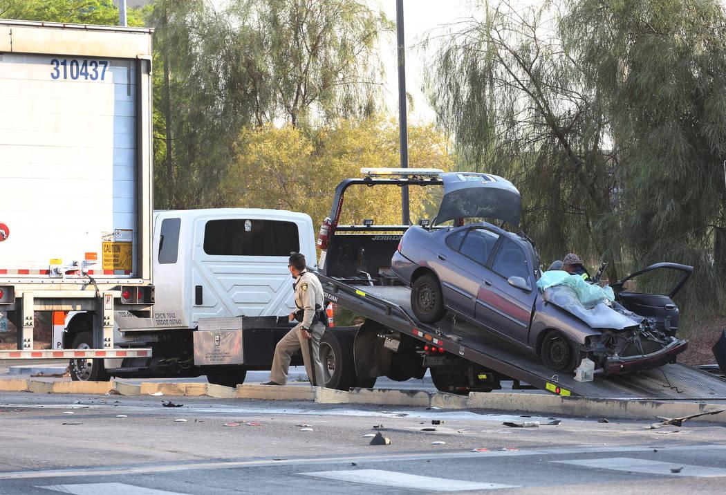 Un automóvil está siendo remolcado después de haber estado involucrado en un accidente con un semirremolque, a la izquierda, en la esquina de Spencer Street y Serene Avenue el miércoles 8 de a ...