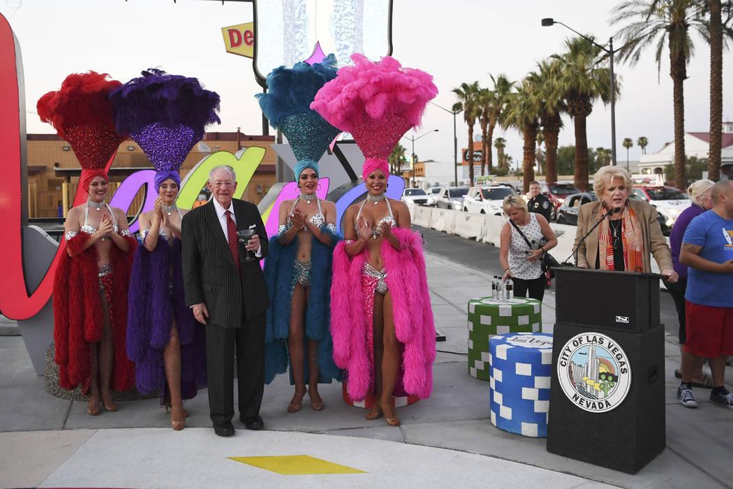 La alcaldesa de Las Vegas, Carolyn Goodman, habla mientras el presidente del Comité Organizador de LVCVA, Oscar B. Goodman, posa con showgirls mientras se inaugura un nuevo letrero de Las Vegas e ...