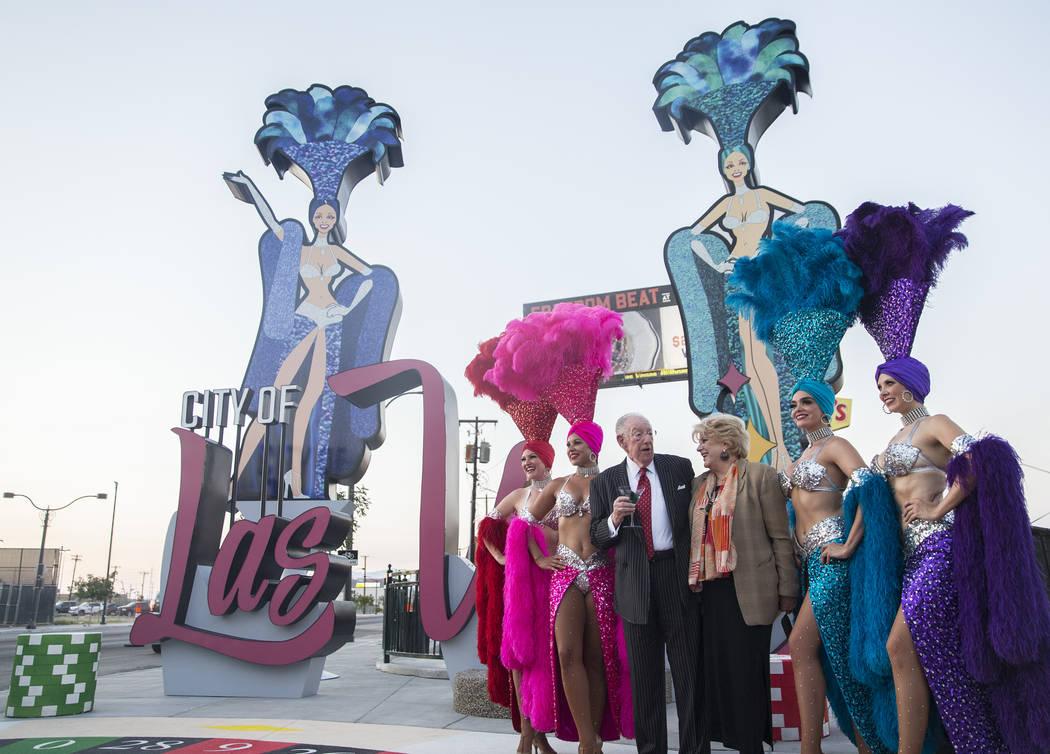La alcaldesa de Las Vegas, Carolyn Goodman, tercera desde la derecha, se toma fotos con su esposo y ex alcalde de Las Vegas, Oscar Goodman y un grupo de showgirls durante una ceremonia de dedicaci ...