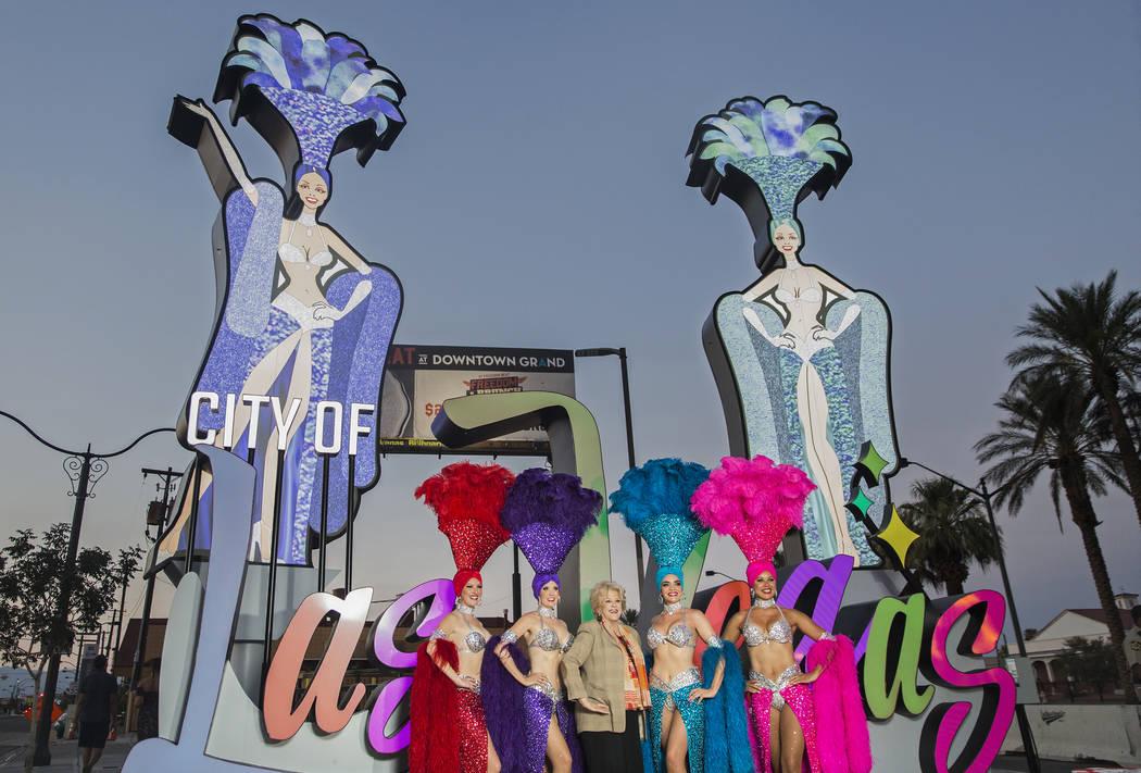La alcaldesa de Las Vegas, Carolyn Goodman, tercera desde la izquierda, se toma fotos con un grupo de showgirls durante una ceremonia de inauguración para la nueva puerta de entrada de la ciudad ...