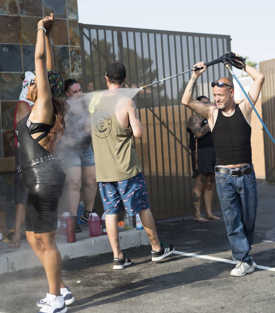 Manuel Serros, propietario de la empresa de lavado móvil, rocía a Dayna Alvarado, hermana de Brandon Steckler, en un lavadero de autos en The Drop en Las Vegas con el objetivo de recaudar dinero ...