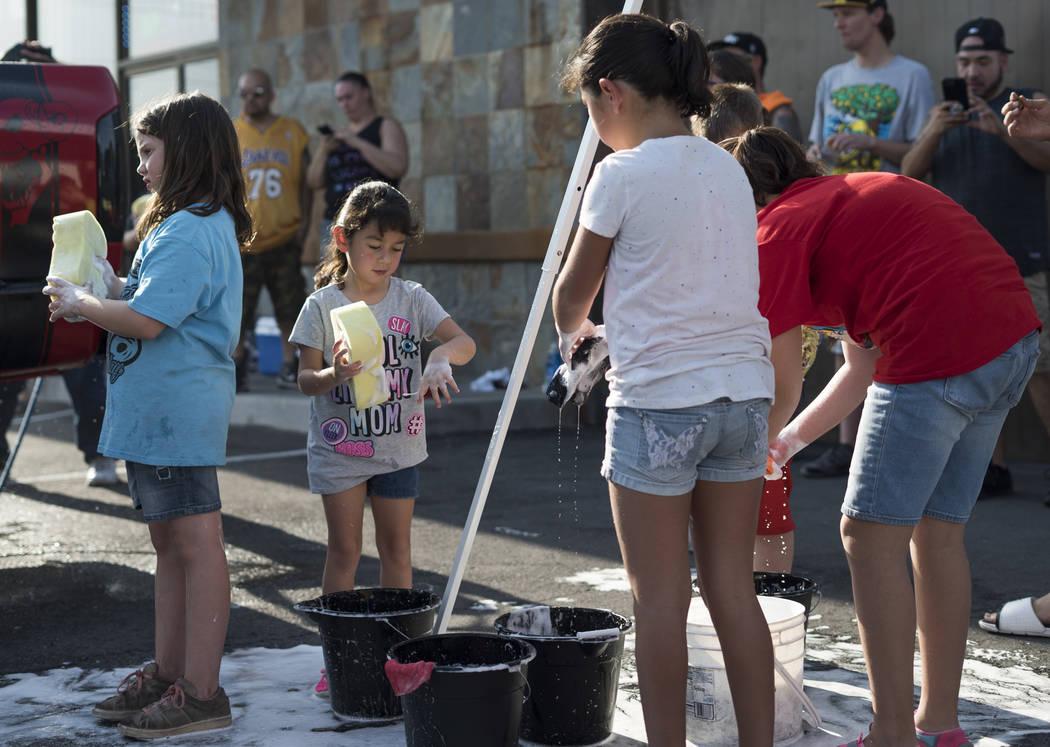 Sallie Valtierra, 5, segunda desde la izquierda, ayuda a recaudar dinero para pagar los gastos del funeral de Brandon Steckler Jr. en The Drop en Las Vegas, jueves, 9 de agosto de 2018. Steckler J ...