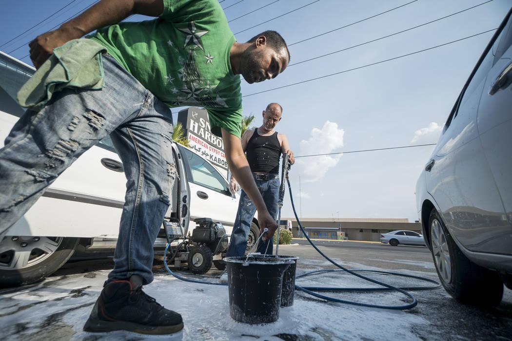 Brandon Steckler, izquierda, y Manuel Serros, propietario de la empresa de lavado móvil, preparan jabón en un lavadero de autos en The Drop en Las Vegas para recaudar dinero para ayudar a pagar ...