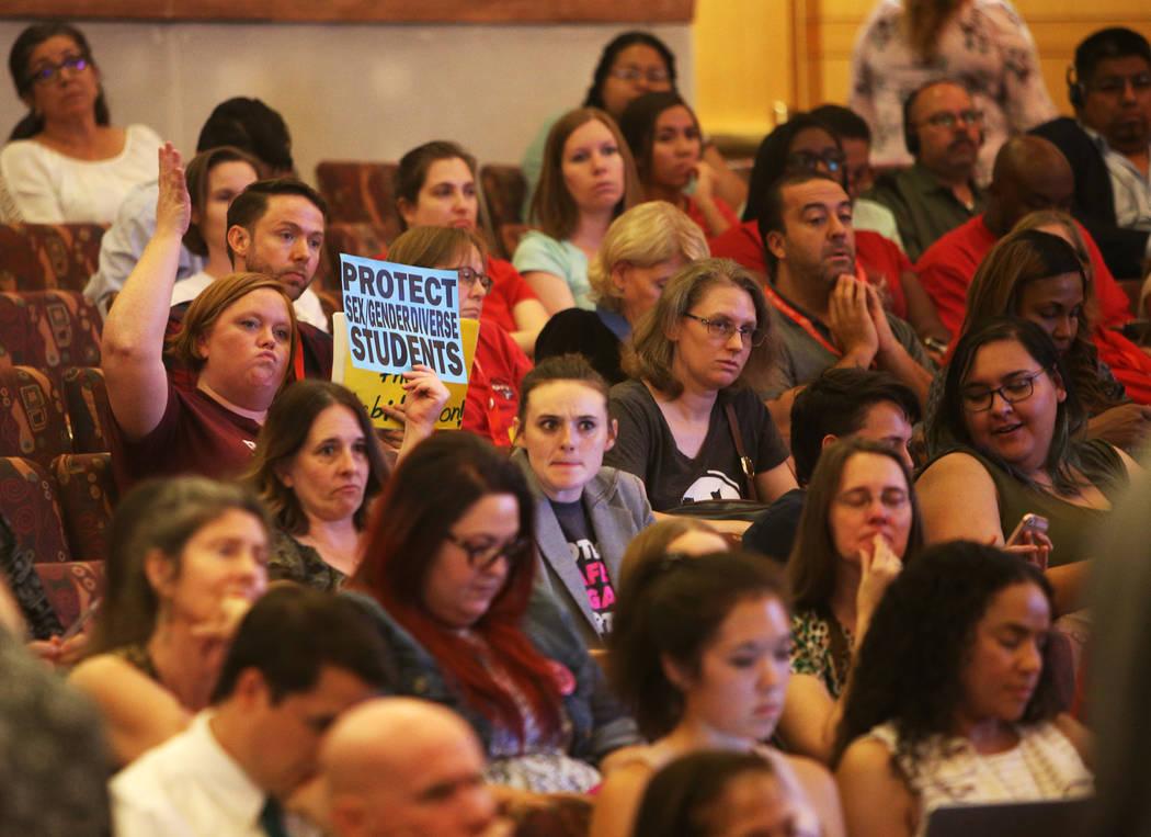 """Una persona sostiene un letrero que dice: """"protejan la diversidad sexual de género de los estudiantes"""" en una reunión de la junta del Clark County School District en el Clark County Government C ..."""