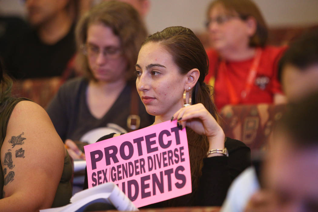 """Caity Gwin sostiene un letrero que dice: """"protejan la diversidad sexual de género de los estudiantes"""" en una reunión de la junta del Clark County School District en el Clark County Government Ce ..."""