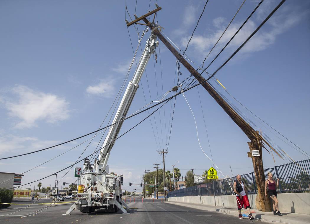Los residentes de Las Vegas pasan cerca de los equipos de NV Energy que trabajan para restaurar la energía en el área de Fremont Street y Bruce Street el domingo, 12 de agosto de 2018, en Las Ve ...