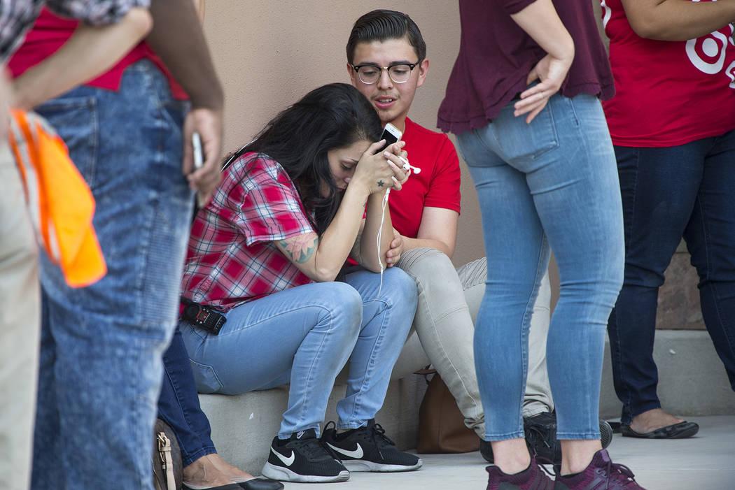 Empleados de Target no identificados se consuelan unos a otros mientras la policía de Las Vegas investiga un tiroteo en un complejo comercial cerca de Blue Diamond Road y Arville Street en Las Ve ...