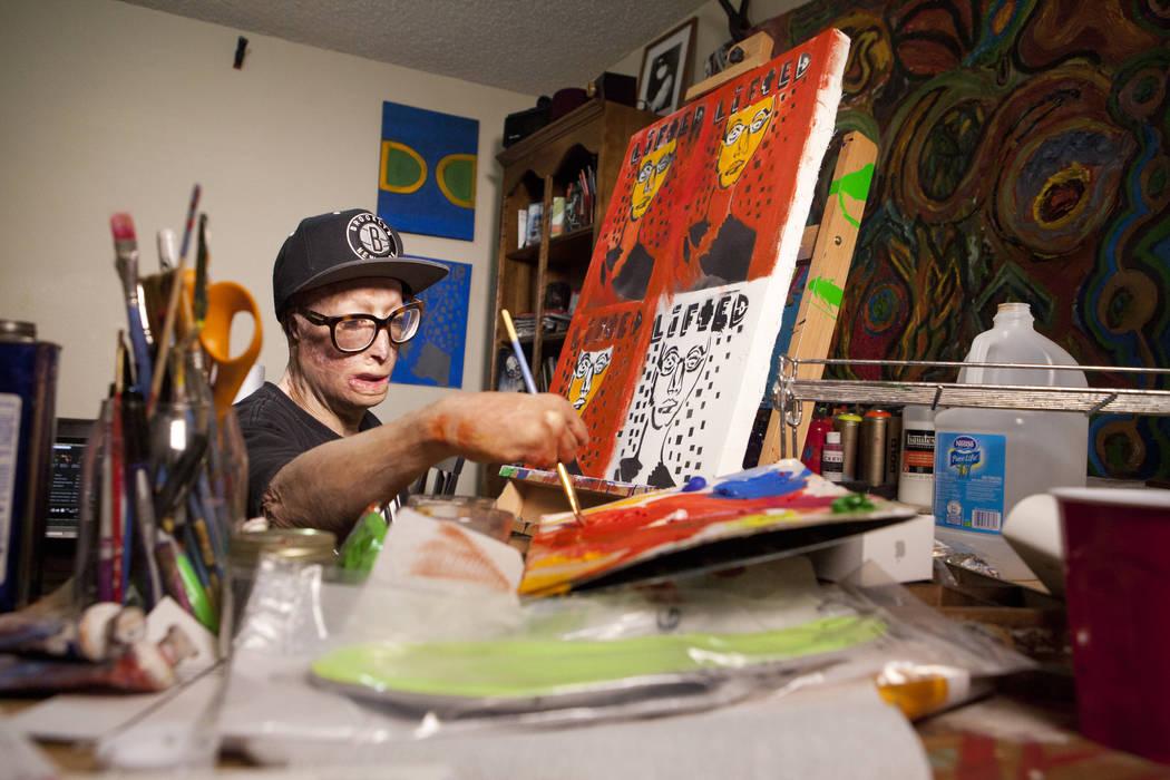 """El artista Dave Dave trabaja en su serie de pintura """"Lifted"""" en su apartamento de Las Vegas el miércoles 20 de junio de 2016. Su padre intentó matarlo cuando tenía seis años al prenderle fuego ..."""