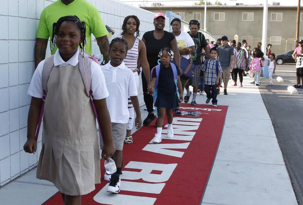 Los alumnos de la escuela primaria Matt Kelly y sus padres caminan sobre la alfombra roja cuando llegan el primer día de clases el lunes 13 de agosto de 2018 en North Las Vegas. Bizuayehu Tesfaye ...