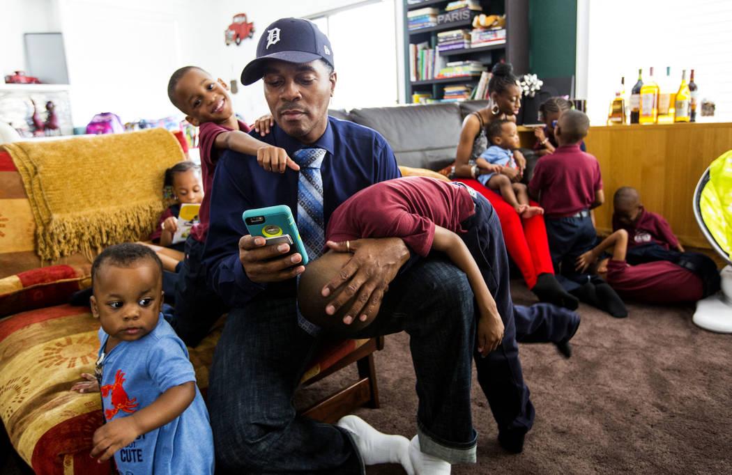 Deon Derrico revisa su teléfono mientras está sentado con sus hijos, desde la izquierda, Dior, 1, Deniko, 4 y Denver, 6, en su casa en North Las Vegas el miércoles, 15 de agosto de 2018, mientr ...