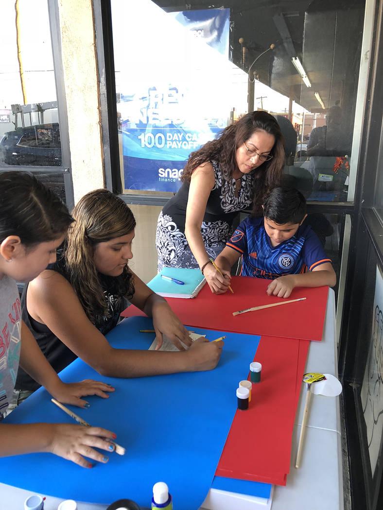 Sandra Granados (de pie) ayuda, el 15 de agosto de 2018, a niños a preparar pancartas de apoyo a la campaña por el TPS. Foto Valdemar González / El Tiempo - Contribuidor.