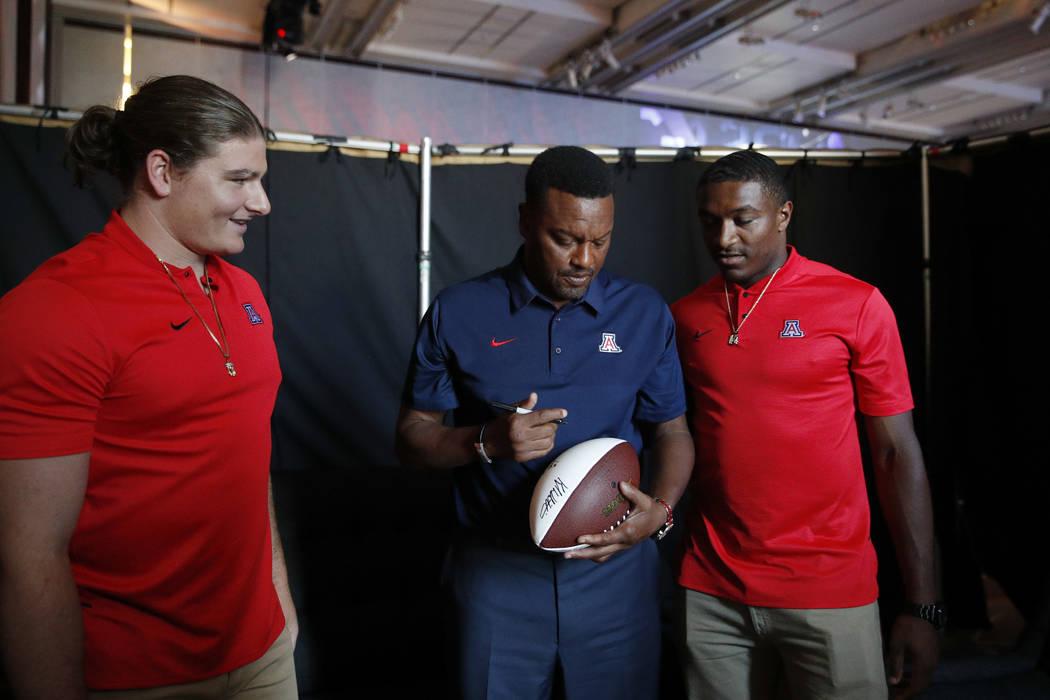 Flanqueado por el linebacker Colin Schooler, izquierda, y el mariscal de campo Khalil Tate, el entrenador de Arizona, Kevin Sumlin, firma su autógrafo en la conferencia Pac-12 NCAA football footb ...