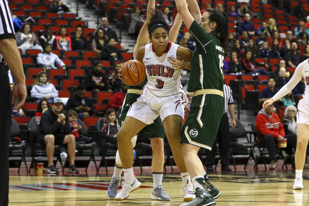 Paris Strawther (3), jugadora de las UNLV Rebels como delantera/centro, driblea el balón contra la alera de los Rams del Estado de Colorado: Veronika Mirkovic (15), durante un juego de baloncesto ...