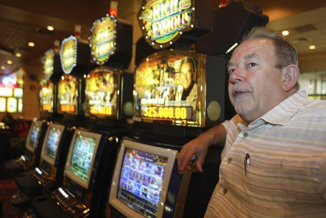 """Robin Leach se encuentra al lado de una máquina tragamonedas """"Rica y famosa"""" dentro de The Orleans en Las Vegas, julio de 2004. (Clint Karlsen / Las Vegas Review-Journal)"""