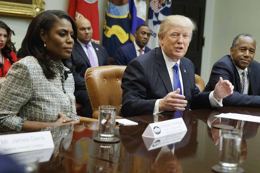 El presidente Donald Trump, en el centro, está flanqueado por el miembro de la Casa Blanca Omarosa Manigault Newman, izquierda, y el entonces designado secretario de Vivienda y Desarrollo Urbano, ...