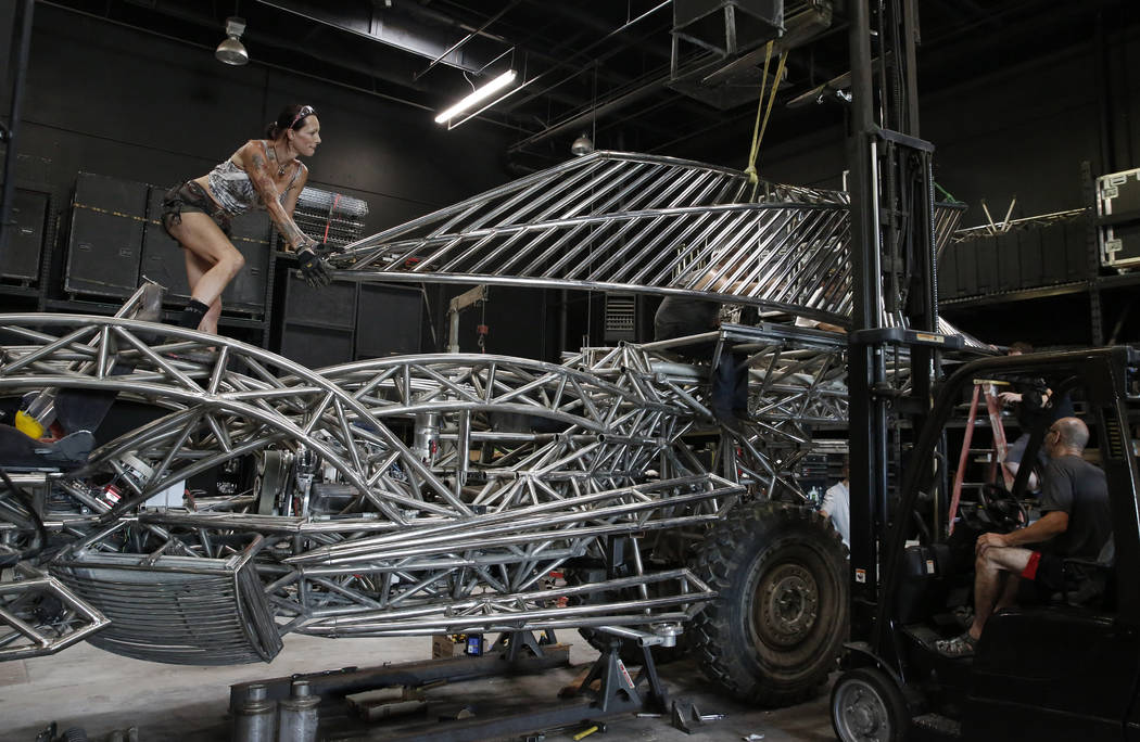 El martes 14 de agosto de 2018, en Las Vegas, la tripulación, incluida Carmen Cole, izquierda, cabeza pulidora, iza el riel de pasajeros para montarlo en el vehículo Flux Capacitor en el garaje ...