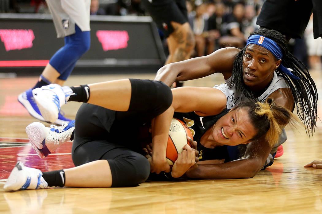 La guardia de las Aces de Las Vegas, Kayla McBride (21), agarra el balón de la centro de las Lynx de Minnesota, Sylvia Fowles (34), en un partido de baloncesto de la WNBA en el Mandalay Bay Event ...
