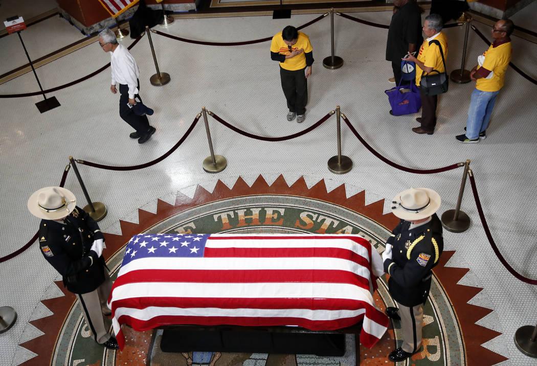 Un grupo vietnamita del Condado de Orange, California, presenta sus respetos cerca del ataúd del senador John McCain durante una visita al Capitolio de Arizona el miércoles 29 de agosto de 2018 ...