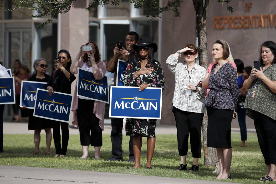 La gente mira una caravana que lleva el ataúd del senador John McCain, republicano por Arizona, mientras viaja desde el Capitolio de Arizona a la Iglesia Bautista del Norte de Phoenix para un ser ...