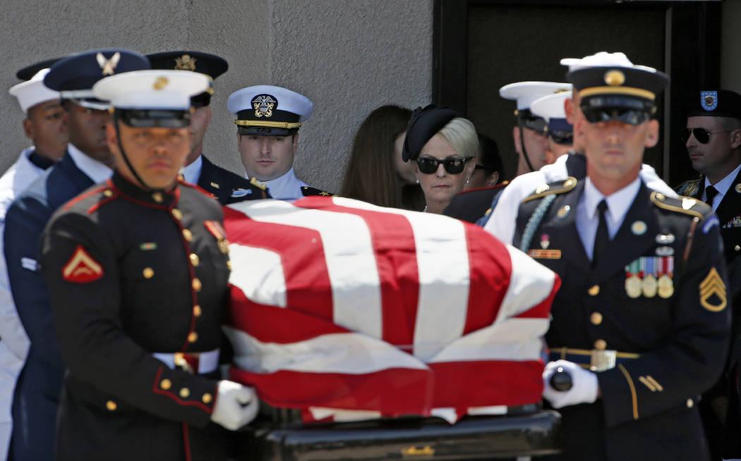 Cindy McCain, a la derecha, camina con su hijo Jack McCain, a la izquierda, mientras siguen a la guardia de honor militar con el féretro del senador John McCain, R-Ariz., Después de un funeral e ...