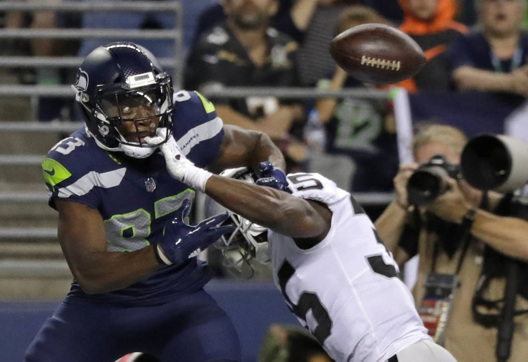 El receptor abierto de los Seattle Seahawks ,David Moore, izquierda, mira el balón después de que Shareece Wright, derecha defensiva de los Oakland Raiders, rompió el pase durante la primera mi ...