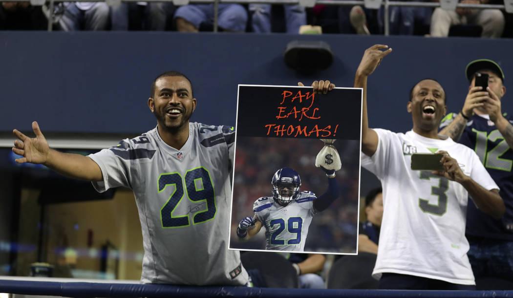 """Un fan sostiene un letrero que dice """"¡Paga Earl Thomas!"""" durante un partido de pretemporada de fútbol de la NFL contra los Raiders de Oakland, el jueves 30 de agosto de 2018 en Seattle. Thomas, ..."""