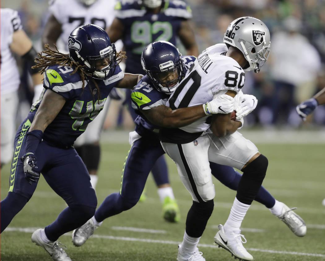 El linebacker de los Seattle Seahawks, Shaquem Griffin, izquierda, y el defensa, Dontae Johnson (39), tacklean al receptor de los Oakland Raiders, Saeed Blacknall (80) durante la primera mitad de ...