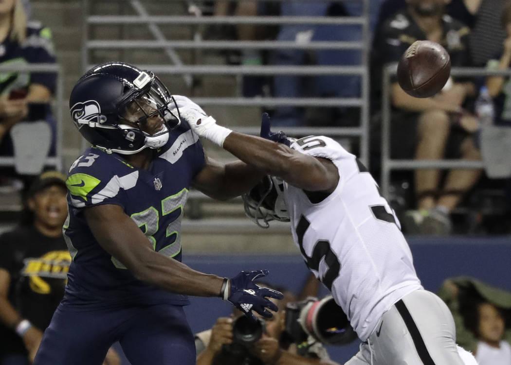 El receptor abierto de los Seattle Seahawks, David Moore, izquierda, mira el balón después de que Shareece Wright, derecha defensiva de Oakland Raiders, rompió el pase pero fue interceptada dur ...