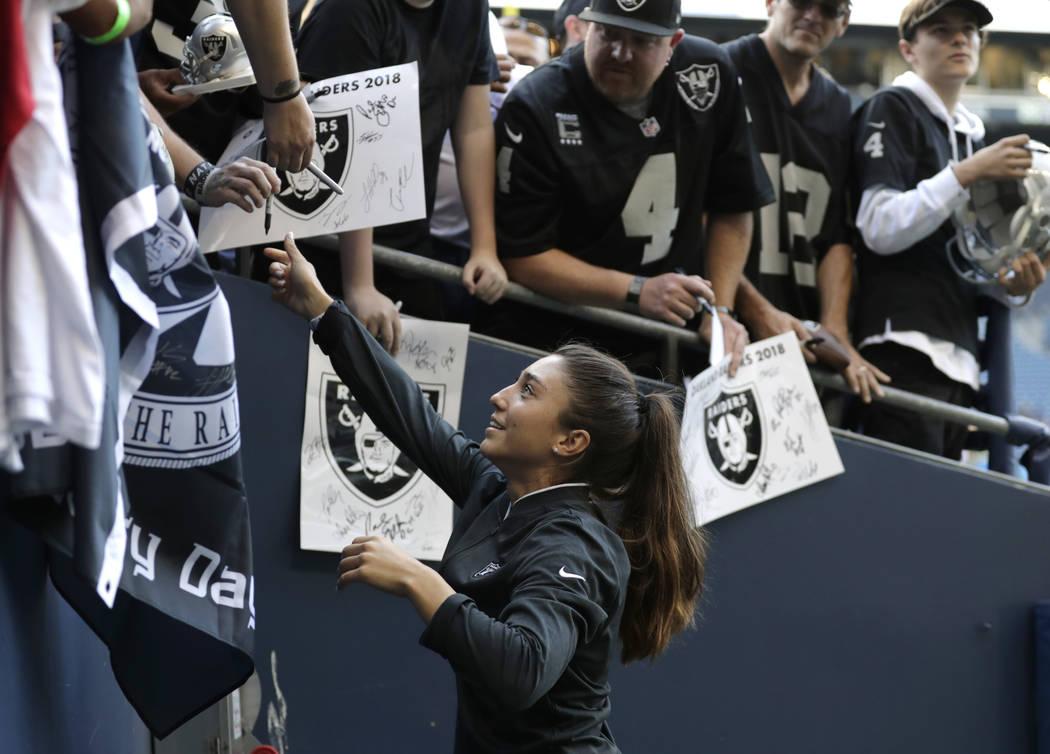 Kelsey Martínez, el entrenador asistente de fuerza y acondicionamiento de los Oakland Raiders, firma autógrafos antes de un partido de pretemporada de fútbol de la NFL contra los Seattle Seahaw ...