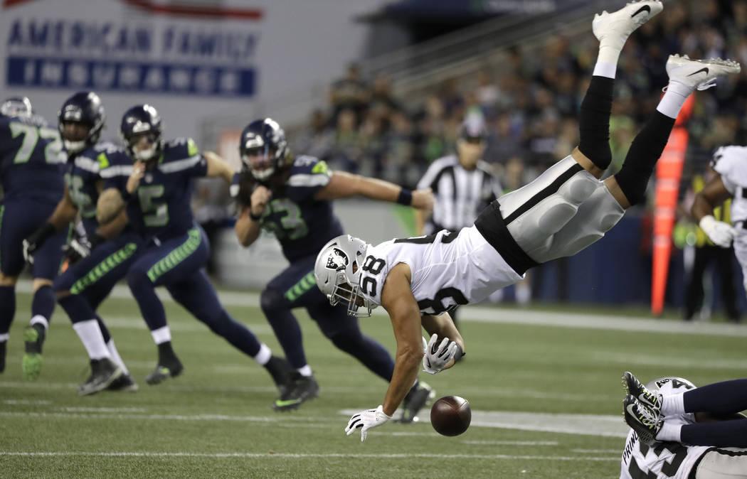 Los jugadores de los Seahawks de Seattle ven cómo el linebacker de los Oakland Raiders, Kyle Wilber (58), intenta interceptarlo pero no puede sostener el balón durante la segunda mitad de un par ...