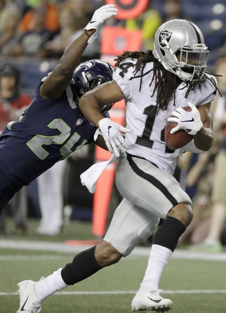 El receptor abierto de los Oakland Raiders, Keon Hatcher, se libera del defensivo de los Seattle Seahawks, Mike Tyson, izquierda, para anotar un touchdown durante la segunda mitad de un partido de ...
