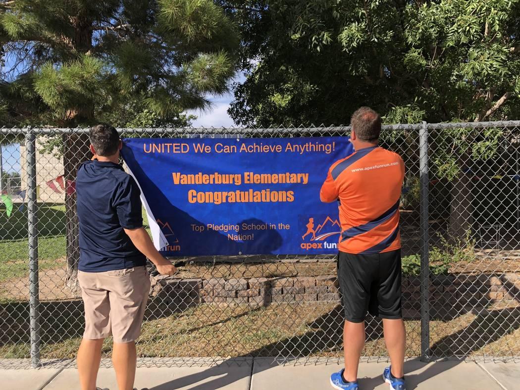 Frank Endellicate y Rob Wiatt, empleados de Apex Fun Run, cuelgan un cartel en la Escuela Primaria Vanderburg en Henderson el 24 de agosto, celebrando el logro de la escuela. Dylan Chalmers, de si ...