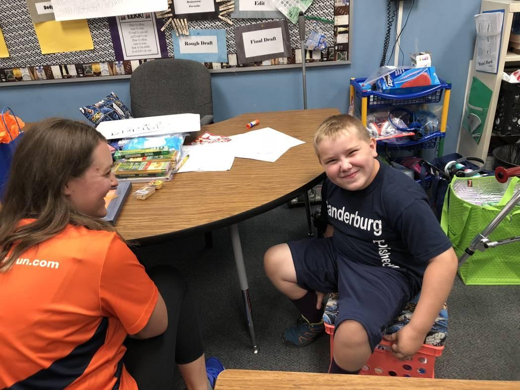 Dylan Chalmers, de siete años, estudiante de segundo grado con parálisis cerebral, trabaja en una computadora después de la escuela en la Primaria Vanderburg con su padre, Scott, el 24 de agost ...
