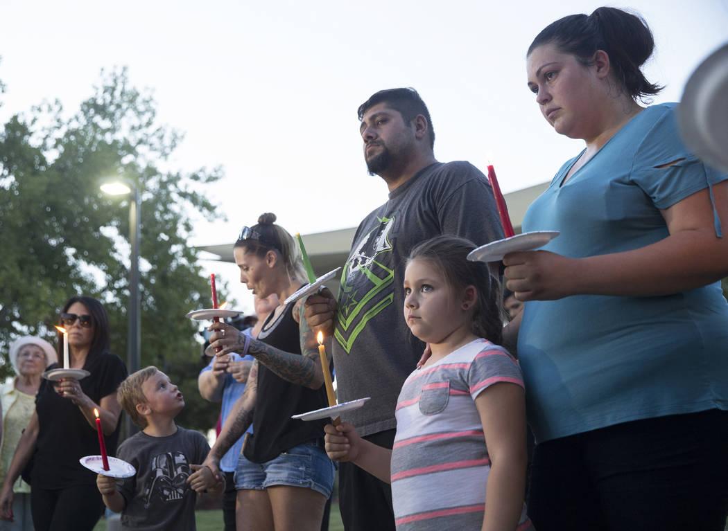 Jasmine González, abajo/derecha, de cinco años, sostiene una vela durante un velorio por Levi Echenique, Daniel Theriot y Dejah Hunt en Sunset Park el martes 4 de septiembre de 2018 en Las Vegas ...
