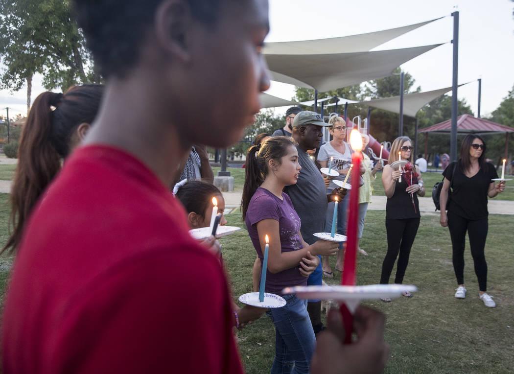 Ares Mendiola, en el centro, de 11 años, sostiene una vela durante un velorio por Levi Echenique, Daniel Theriot y Dejah Hunt en Sunset Park el martes 4 de septiembre de 2018 en Las Vegas. Benjam ...