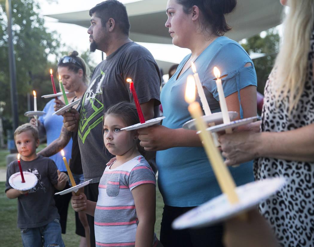 Jasmine González, abajo/medio, 5, sostiene una vela durante un velorio por Levi Echenique, Daniel Theriot y Dejah Hunt en Sunset Park el martes 4 de septiembre de 2018 en Las Vegas. Benjamin Hage ...