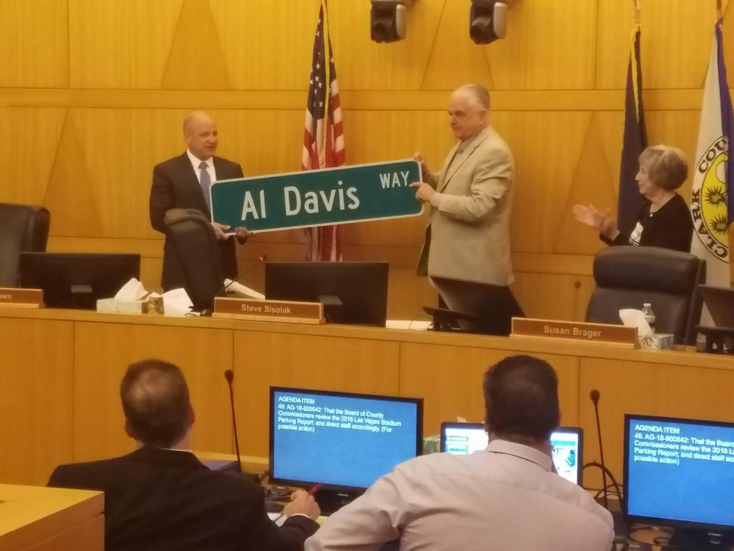 """El presidente de los Raiders de Oakland, Marc Badain acepta una señal de calle para """"Al Davis Way"""" del Comisionado del Condado de Clark Steve Sisolak en una reunión de la Comisión del Condado d ..."""