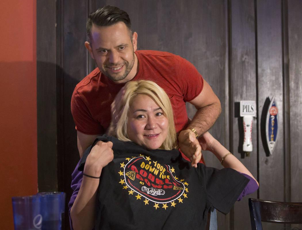 La campeona local y competitiva de comidas de Las Vegas, Miki Sudo, abajo, obtiene su camiseta de Dave Michel después de completar el Double Down Pizza Challenge en Slice of Vegas el jueves 6 de ...