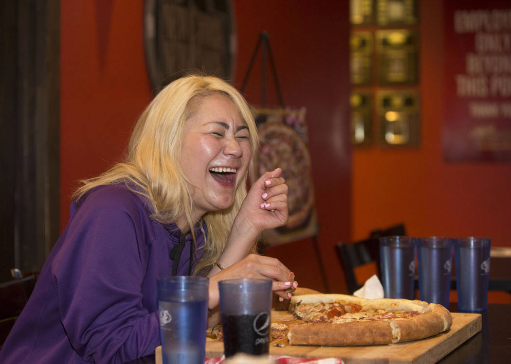 La campeona local y competitiva de comidas de Las Vegas, Miki Sudo, se ríe con sus amigos durante su intento de completar el Double Down Pizza Challenge en Slice of Vegas el jueves, 6 de septiemb ...