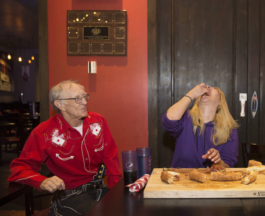 """La campeona local y competitiva de comidas de Las Vegas Miki Sudo, derecha, intenta completar el Double Down Pizza Challenge con el apoyo de su compañero competitivo y amigo Rich """"The Locust"""" LeF ..."""