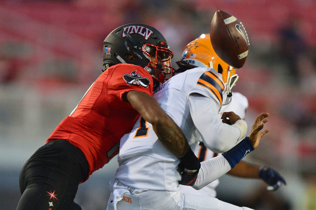UNLV Rebels defensive back Evan Austrie (17) strips the ball away from UTEP Miners quarterback Kai Locksley (1) at Sam Boyd Stadium in Las Vegas on Saturday, Sept. 8, 2018. UNLV leads at halftime ...
