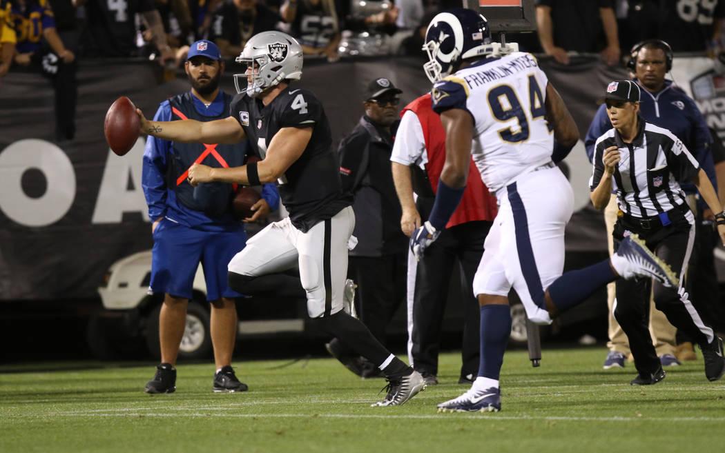 El mariscal de campo de los Oakland Raiders, Derek Carr (4), corre con el equipo cuando el alero defensivo de los Rams de Los Ángeles, John Franklin-Myers, lo persigue durante la primera mitad de ...