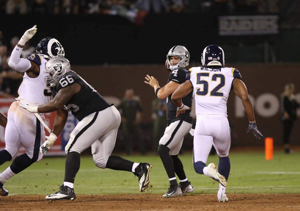 El mariscal de campo de los Oakland Raiders, Derek Carr (4), se prepara para tirar el balón bajo presión del linebacker de los Rams, Ramik Wilson (52), durante la primera mitad de su juego de la ...