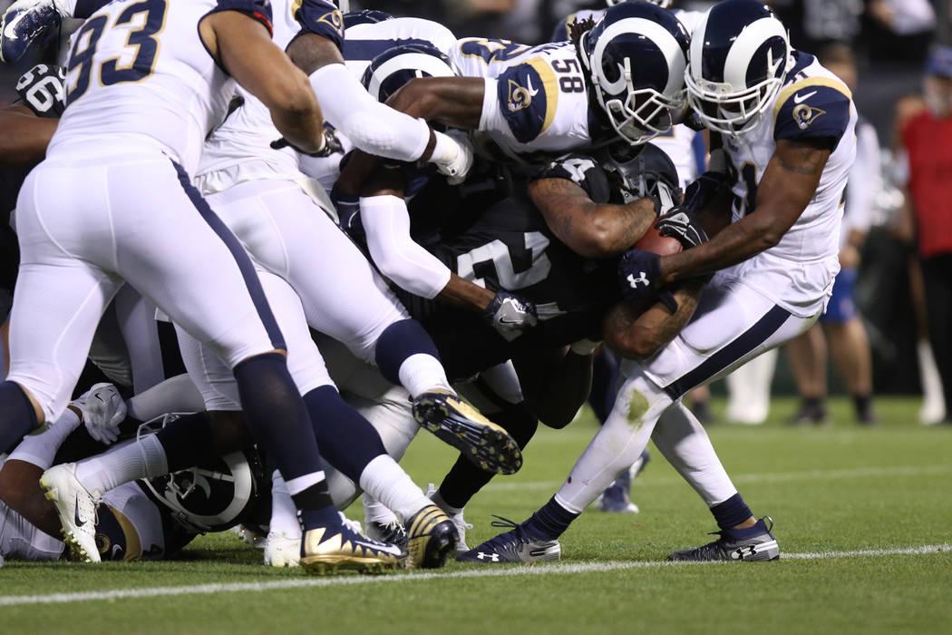 El corredor de Oakland Raiders, Marshawn Lynch (24), empuja a la zona de anotación cuando Aqib Talib (21) defensivo de Los Ángeles Rams y el linebacker Cory Littleton (58) intentan derribarlo du ...