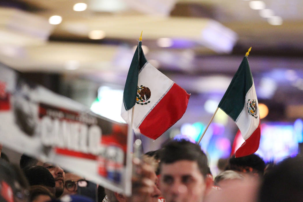 """La gente ondea banderas mexicanas durante un evento de """"Grandes Llegadas"""" de boxeo para Gennady Golovkin y Saúl """"Canelo"""" Álvarez en el hotel-casino MGM Grand en Las Vegas, martes 11 de septiembr ..."""