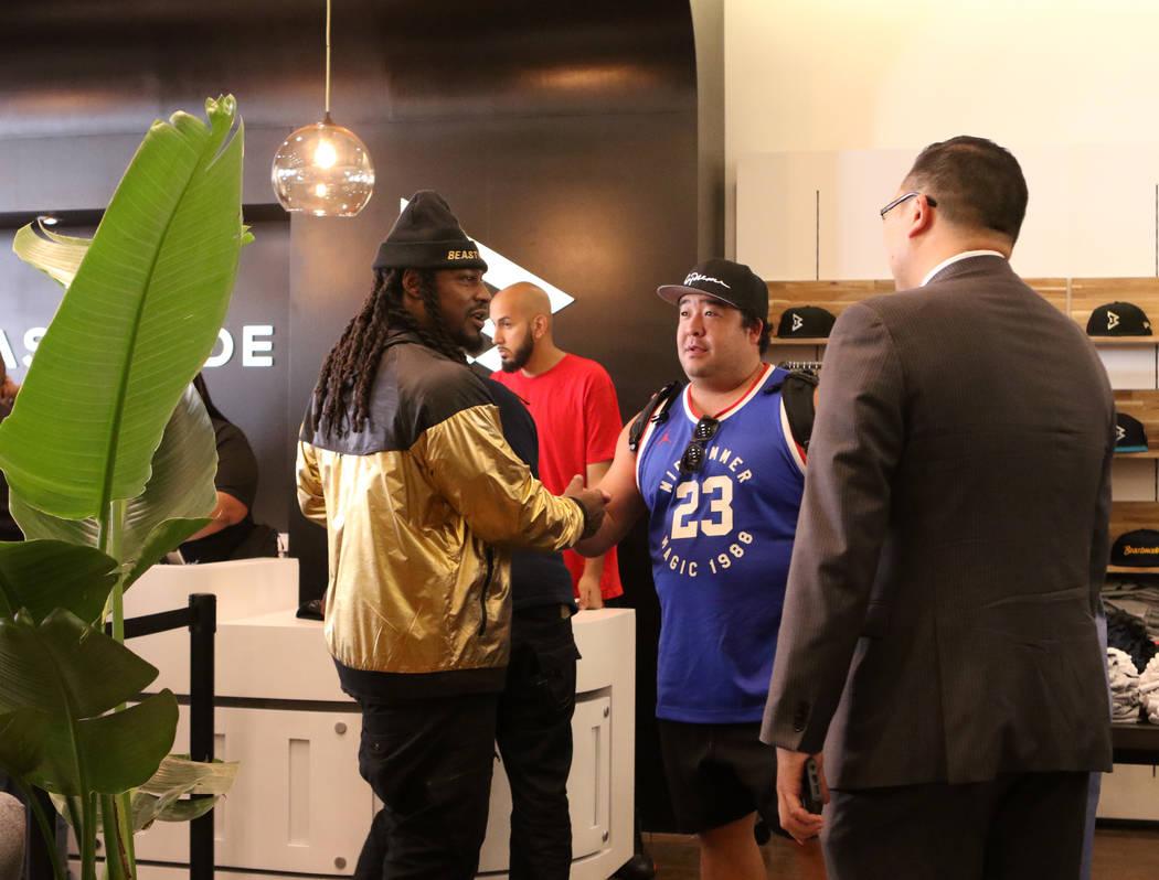 """El corredor de los Oakland Raiders, Marshawn Lynch, se da la mano con un fan durante la gran apertura de su tienda """"Beast mode"""" en Town Square en Las Vegas, el sábado 1 de septiembre de 2018. Hei ..."""
